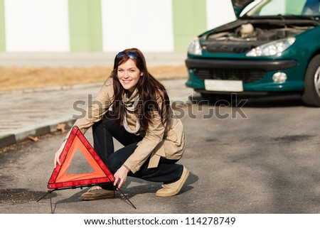 Woman putting warning triangle on the road car breakdown sign - stock photo