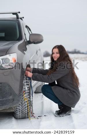 Woman putting winter tire chains on car wheel snow breakdown - stock photo
