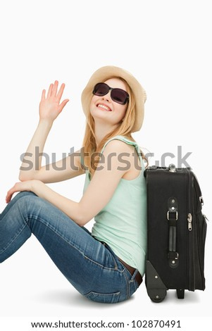Woman rainsing her hand while sitting near a suitcase against white background - stock photo