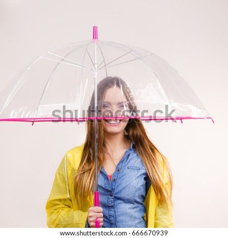 Woman rainy smiling girl wearing waterproof yellow coat standing under umbrella having fun. Meteorology, forecasting and weather season concept