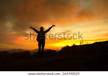woman raising her arms and enjoying the beautiful sunset - stock photo
