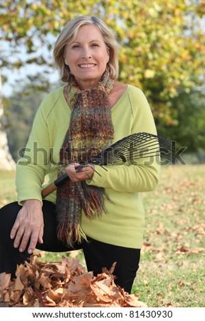 Woman raking leaves in a yard - stock photo