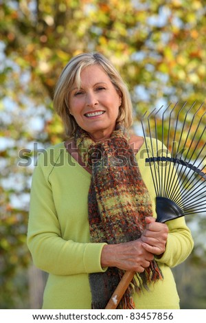 Woman raking leaves in a yard - stock photo