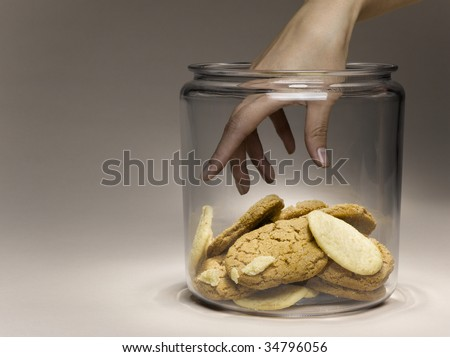 Woman reaching for cookies in cookie jar, close-up of hand - stock photo