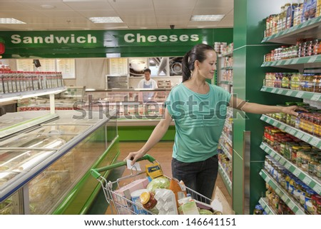 Woman reaching for jar on the shelf in the supermarket, Beijing - stock photo