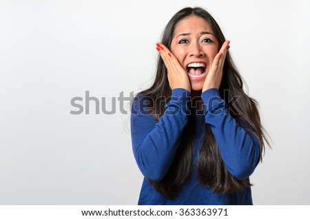 Woman reacting in terror and panic holding her hands to her cheeks as she screams , upper body on white - stock photo