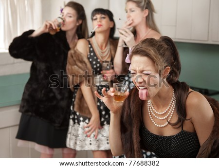 Woman reacts to strong alcohol while friends smoke and drink in the kitchen - stock photo