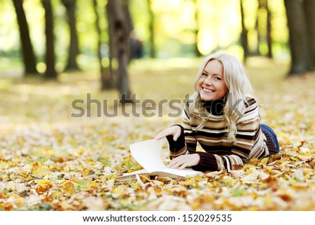 woman read the book in autumn park - stock photo