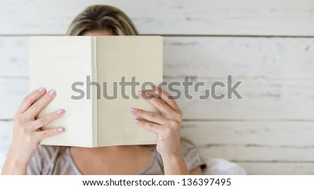Woman reading a book and covering her face - stock photo