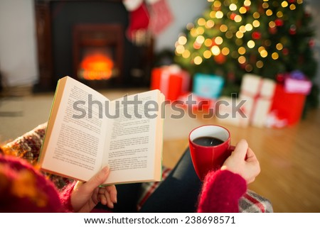 Woman reading a book and drinking coffee at christmas at home in the living room - stock photo