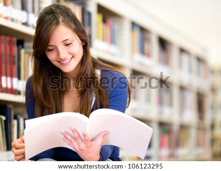 Woman reading a book at the library - stock photo