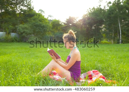 Woman reading a book in a city park on the lawn.