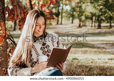 woman reading a book in autumn