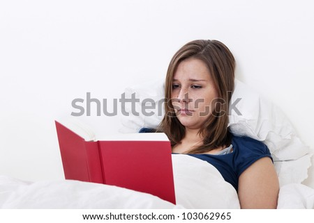 Woman reading a book in bed - stock photo
