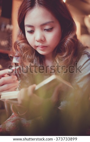 Woman reading a book in coffee shop, Color effect image - stock photo