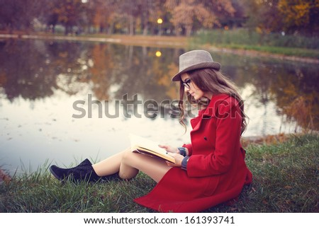 Woman reading a book in the park in autumn  - stock photo