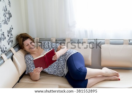 woman reading a book lying on the couch
