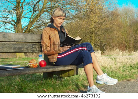 Woman reading a book on a bench outdoors. - stock photo