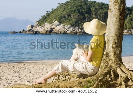 Woman reading a book on a tropical beach - Bombinhas - Brazil - stock photo