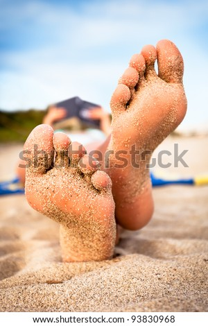 Woman reading a book on the beach. Shallow deep of focus. - stock photo