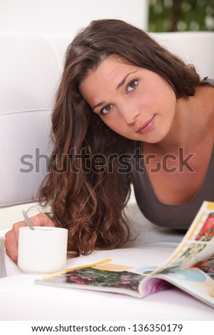 Woman reading a book while drinking a cup of tea - stock photo
