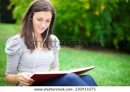 Woman reading a book while listening music in a park