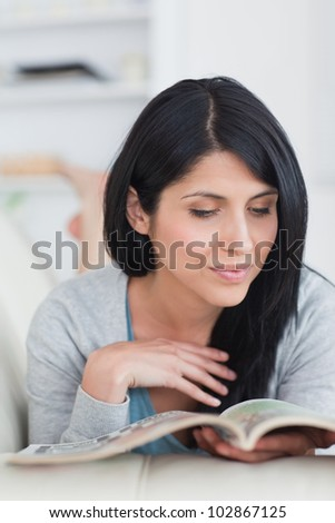 Woman reading a book while lying on a couch and touches her hair in a living room - stock photo