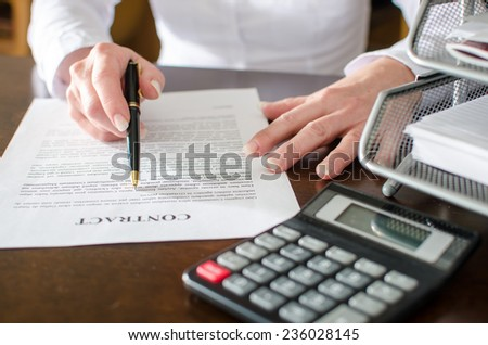 Woman reading a car purchase contract in car dealership - stock photo