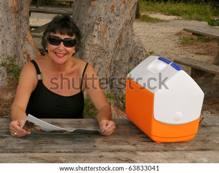 Woman reading a magazine at a picnic table