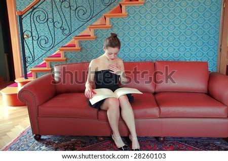 woman reading a magazine on a sofa - stock photo