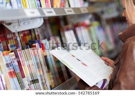 Woman reading a magazine which she has just removed for a display on a shelf in a supermarket - stock photo