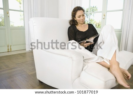 Woman reading a magazine while sitting on an armchair at home. - stock photo