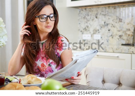 Woman reading a newspaper while holding a cup of tea in the kitchen - stock photo