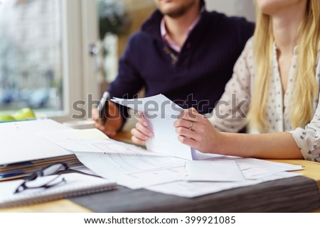 Woman reading a paper document as she sits at a table at home with her husband balancing the books , close up view of her hands and the paperwork - stock photo