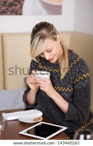 Woman reading an e-book in a cafe sitting at a table with a cup of coffee in her hands and her tablet on the table top - stock photo