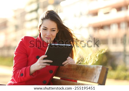 Woman reading an ebook or tablet in an urban park with buildings in the background - stock photo