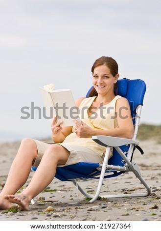 Woman reading book at beach - stock photo