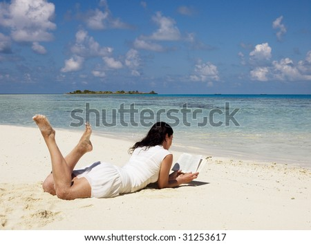 Woman reading book at sandy beach