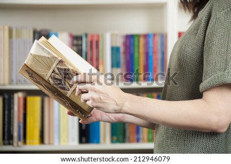 woman reading book green jersey over library background - stock photo