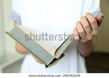 Woman reading book in room - stock photo
