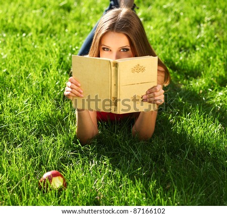 Woman reading book in the park on the grass - stock photo