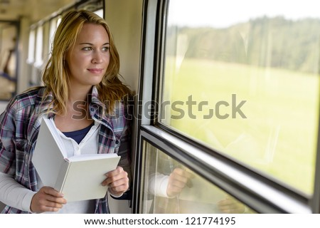 Woman reading book looking out train window smiling vacation traveling - stock photo