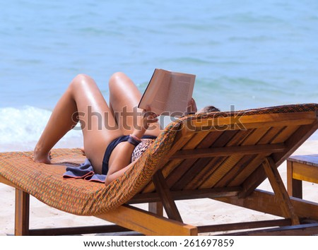 Woman reading book on chaise longue at the seaside - stock photo