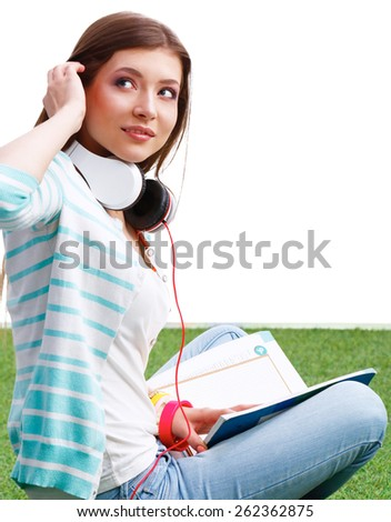 Woman reading book sits on the green grass. - stock photo