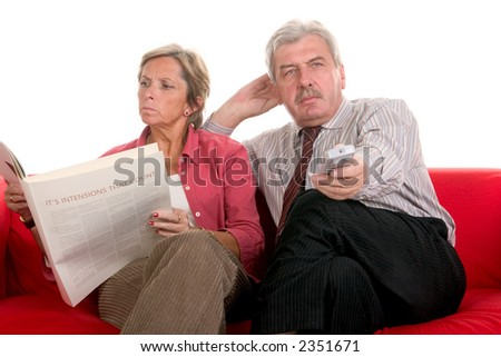 Woman reading book while man watching television - stock photo