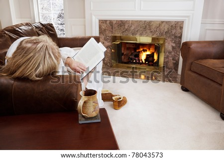 Woman reading by a cozy fire - stock photo