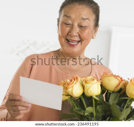 Woman Reading Card with Bouquet of Flowers - stock photo