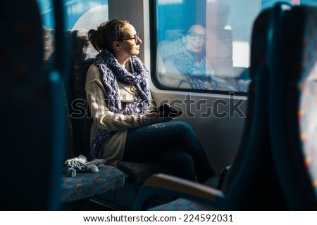 Woman reading ebook on train - stock photo