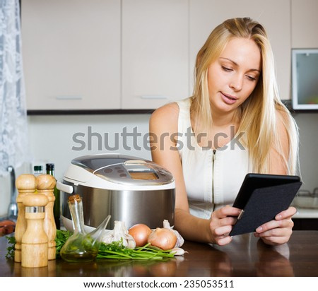 woman  reading ereader and cooking with new crockpot at home interior - stock photo