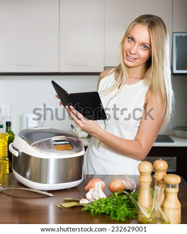 Woman reading ereader while with new electric multicooker doing food at home - stock photo